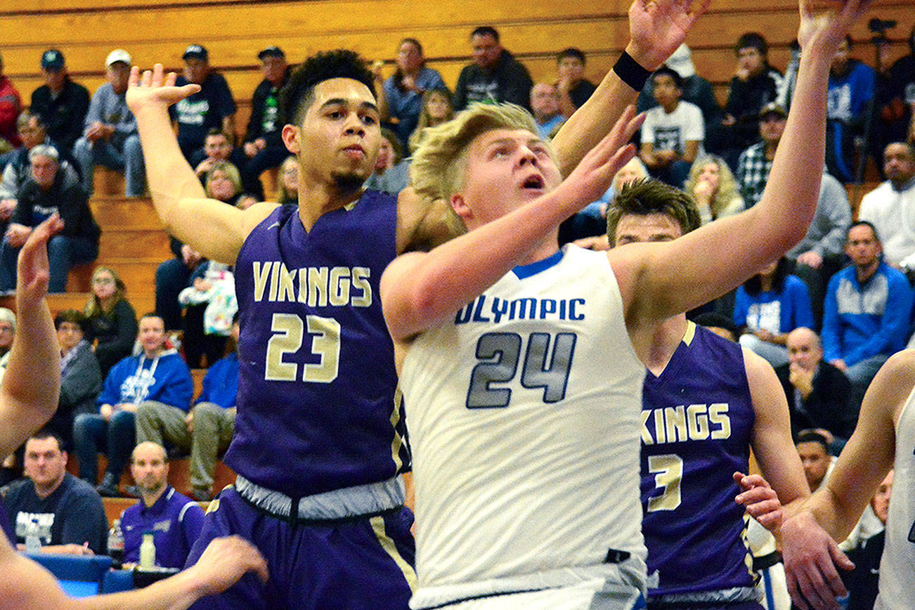 Olympic's Greg Brehmer (24) goes up for a basket as North Kitsap's Shaa Humphrey (23) tries to block it. Brehmer scored ten points for the Trojans and was one of many players who stepped up in the 55-50 victory. (Mark Krulish/Kitsap News Group)