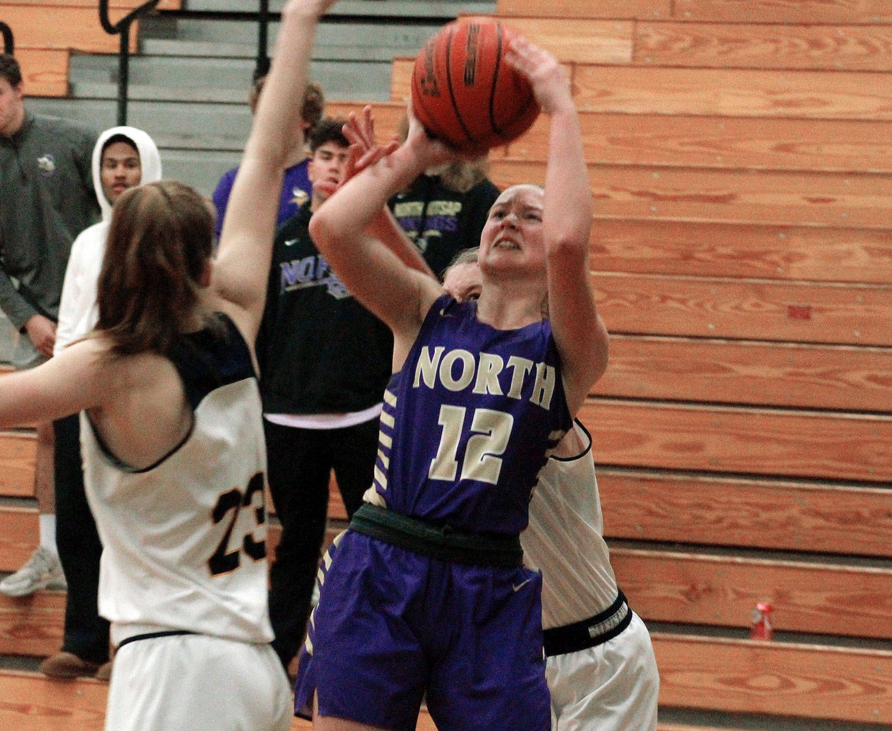 North Kitsap's Grace Johnson takes a shot over Ellie Woolever of Bainbridge (23) in her team's 53-45 victory on Dec. 9. (Mark Krulish/Kitsap News Group)